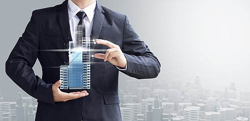 Mann in Anzug hält ein Immobilien-Modell in den Händen